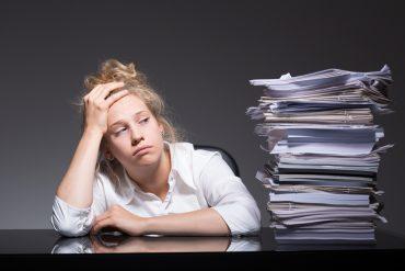 Kvinne på kontor med papirbunke