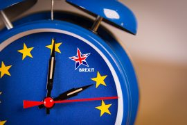 Alarm clock with the colors of the EU flag and one UK star. Representing the countdown for Brexit negociations and strategy concept between European Union and United Kingdom.