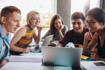 Unge forskere rundt en bærbar PC