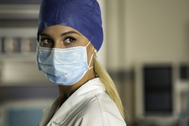 Young blonde nurse in ER room in a surgical mask and surgical cap