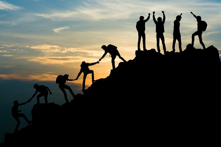 Mennsker som hjelper hverandre opp på en fjelltopp
