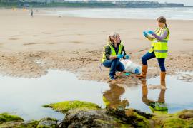 Forskere tar vannprøver på strand