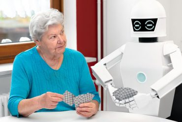 Woman playing cards with robot