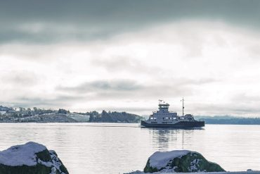 Ferry crossing on a grey winter day with snow on the surrounding islands. It is a hybrid ferry mostly driven by electricity, being charged at a wireless changing station during one of the stops.