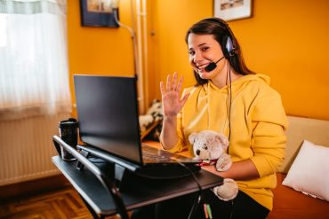 Young smiling woman working from home on laptop. Holding teddy bear.
