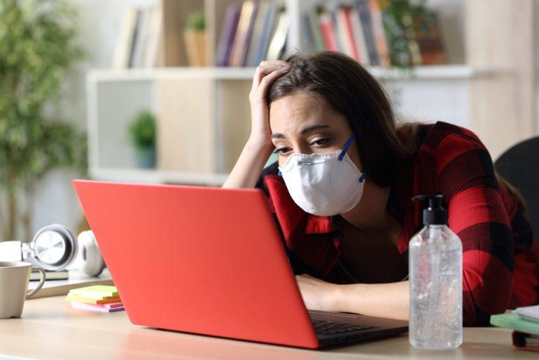 Bored student looking laptop in coronavirus confinement