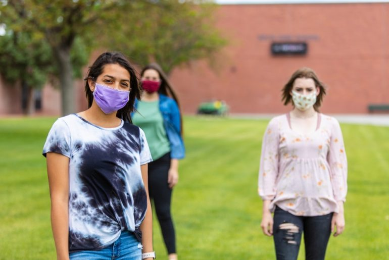 Group of Generation Z Multi-Ethnic Female Friends Wearing Face Masks and Social Distancing